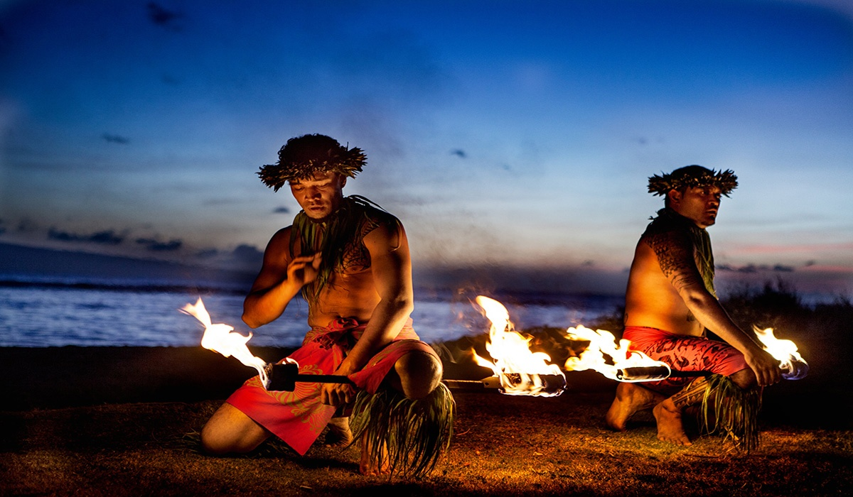 Hawaiian fire dancers in front of sunset