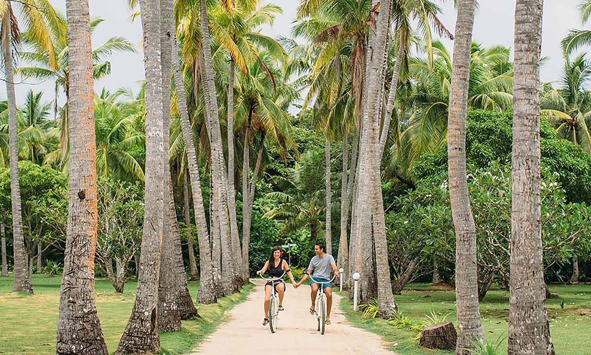 couple holding hands riding bikes on lomani island resort