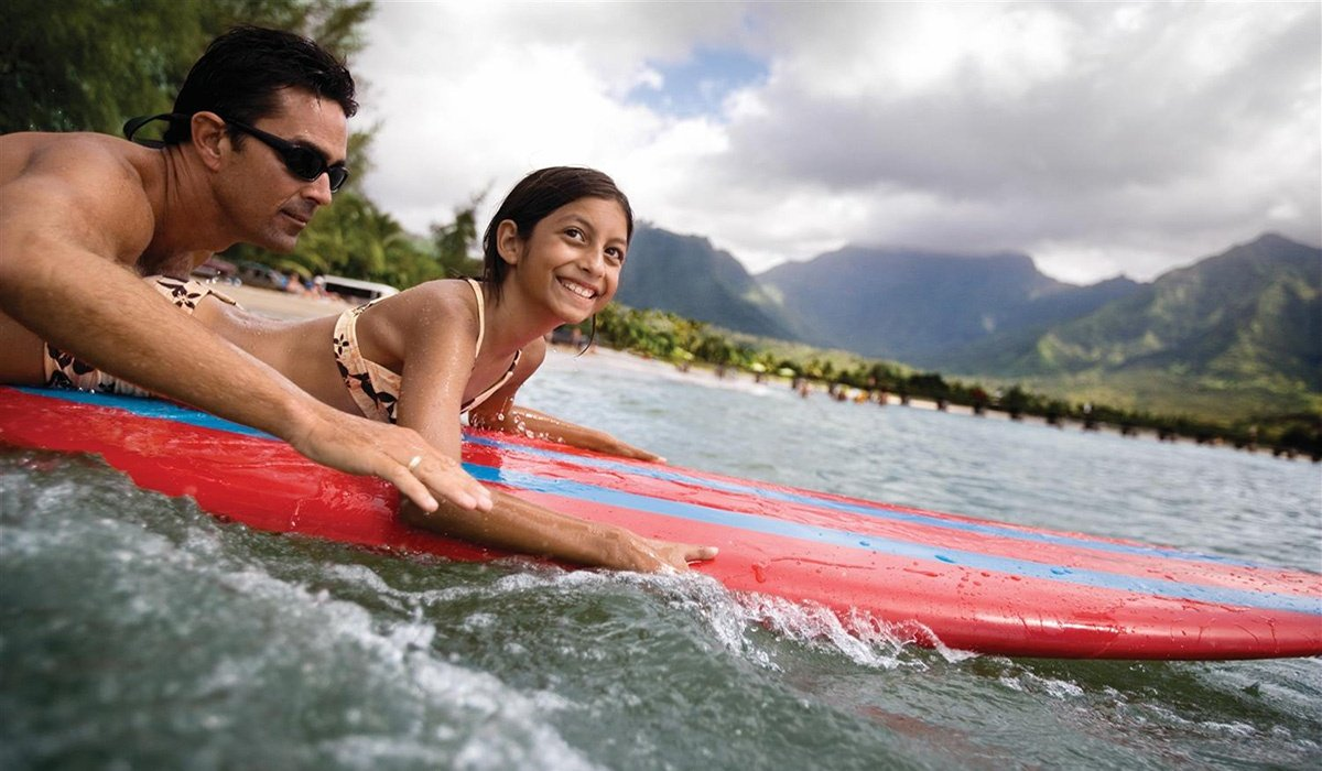 NCL Hawaii two people surfing in front of island