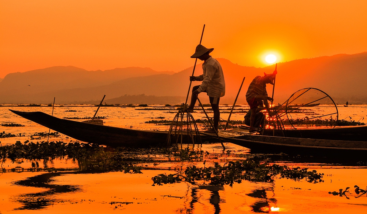Scenic Myanmar (Burma) fishermen on boats at orange sunset