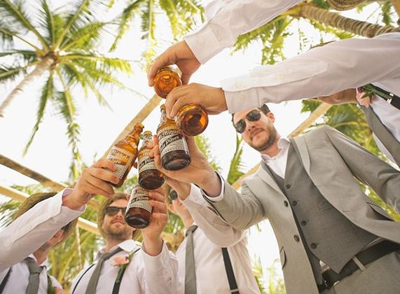 Groomsmen cheers beer under palm trees