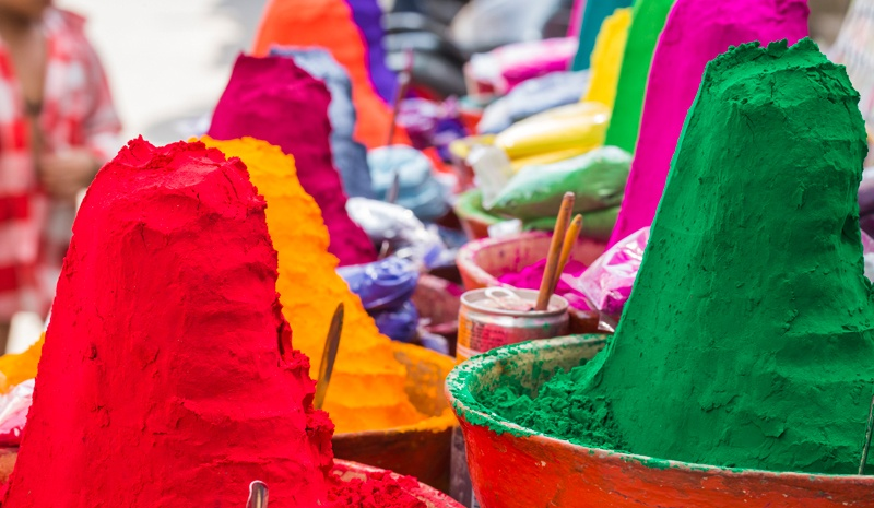 piles of colorful gulal powder in pots